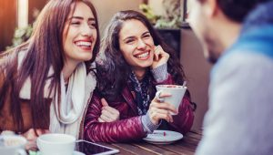 Two young women smiling and talking with a man in a coffee shop.